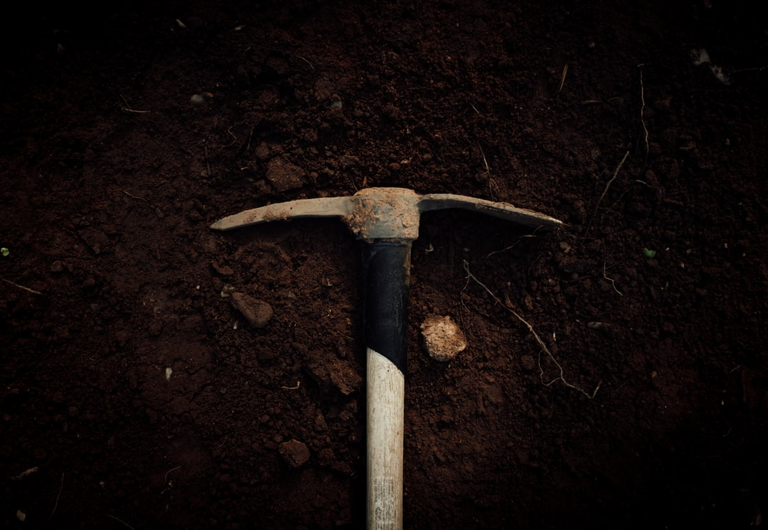 A knife sitting on top of a dirt field